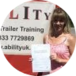 girl showing her driving test pass certificate standing by the car and trailer